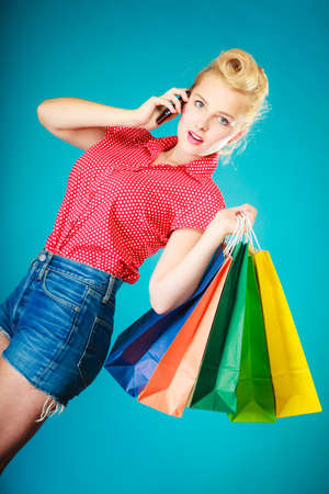 Pinup blond girl surprised woman in retro style calling on the mobile phone. Client customer holding colorful paper shopping bags on vibrant blue. Retail and sale. Studio shot. photo