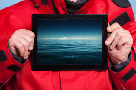 Closeup of male hands holding ipad with photo of stormy sea. Man showing screen tablet touchpad dreaming about holiday vacation. Technology and travel. photo