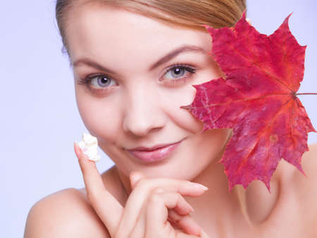 capillary: Skincare habits. Face of young woman with leaf as symbol of red capillary skin on violet. Girl taking care of her dry complexion applying moisturizing cream. Beauty treatment. Stock Photo