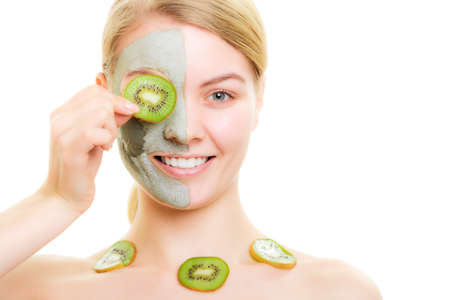wellfare: Skin care. Woman in clay mud mask on face and necklace with kiwi fruit isolated. Girl taking care of dry complexion. Stock Photo