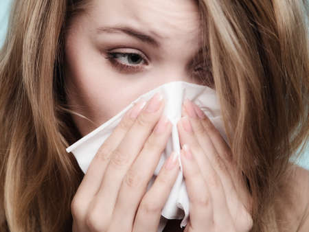cold: Flu cold or allergy symptom. Sick woman girl sneezing in tissue on blue. Health care.