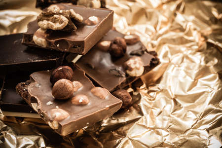 Closeup different sorts chocolate pieces and hazelnuts. Variety of chocolates on golden foil wrapping. photo