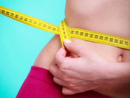 허리의 잘룩 한 선: 다이어트 슬리밍 체중 감소를위한 시간. 보건 의료 및 건강 영양. 블루, 그린에 그녀의 허리를 측정 측정 테이프로 젊은 피트 니스 여자 맞는 여자 스톡 사진