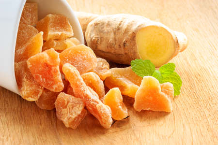 crystallized: Closeup dried candied crystallized ginger pieces and raw root on wooden table. Healthy food, home remedy for nausea, colds.