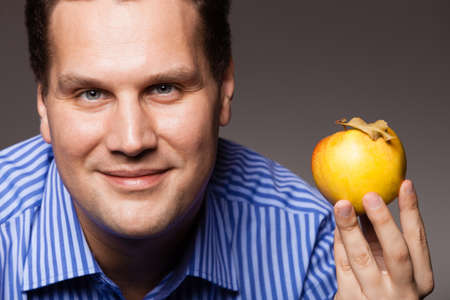 recommending: Diet and nutrition. Happy young man holding apple seasonal fruit on dark gray. Guy recommending healthy nutrition.