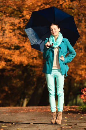 Happiness freedom and people concept. Casual young woman teen girl walking relaxing with blue umbrella in autumnal park, outdoor photo