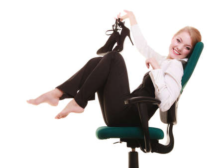 Break from work. Young businesswoman happy girl with shoes in hand relaxing on chair isolated on white. Business. photo