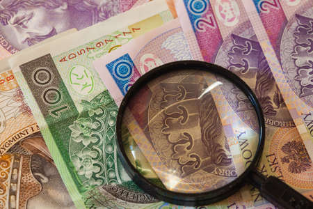 dinero falso: Concepto de dinero falso. Polaco billetes zloty moneda y lupa