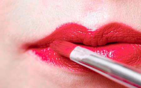 Cosmetic beauty procedures and makeover concept. Closeup part of woman face red lips. Make-up artist applying lipstick with accessories tools.