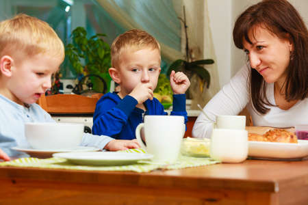 Happy family. Mother and sons boys kids children eating corn flakes and bread breakfast morning meal together at the table. Home. photo