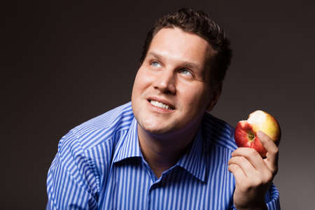 recommending: Diet and nutrition. Happy young man eating apple seasonal fruit on dark gray. Guy recommending healthy nutrition.