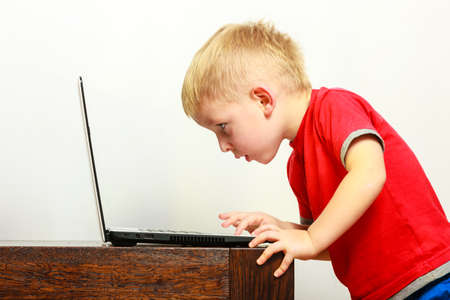 Children, technology and home concept  - little boy kid child using laptop pc computer at home photo