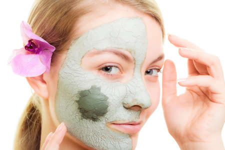 wellfare: Skin care. Woman in clay mud mask on face isolated on white. Girl taking care of dry complexion. Beauty treatment. Stock Photo