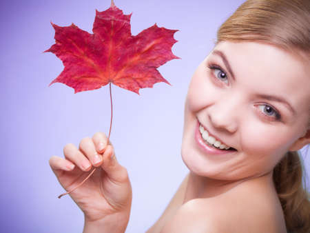 wellfare: Skincare habits. Portrait of young woman with leaf as symbol of red capillary skin on violet. Face of girl taking care of her dry complexion. Studio shot. Stock Photo