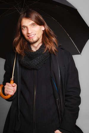 mann mit langen haaren: M�nner Wintermode. Stattlicher Mann, langen Haaren tragen schwarzen Mantel. Casual-Look mit Regenschirm. Studio shot auf grauem