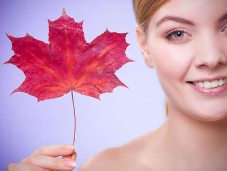 capillary: Skincare habits. Portrait of young woman with leaf as symbol of red capillary skin on violet. Face of girl taking care of her dry complexion. Studio shot. Stock Photo