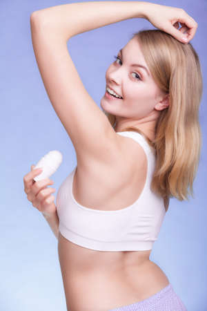underarms: Girl applying stick deodorant in armpit. Young woman putting antiperspirant in underarms on blue. Daily skin and body care. Studio shot.
