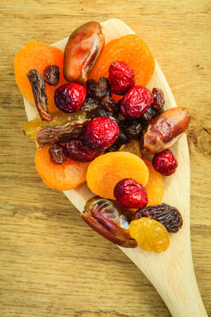 fiber food: Healthy high fiber food, organic nutrition. Closeup different varieties mix of dried fruits on wooden spoon.