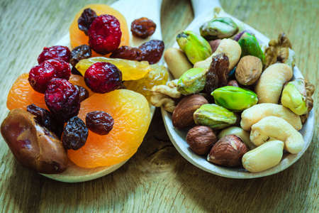 Healthy food organic nutrition. Closeup different varieties mix of dried fruits and nuts on wooden spoons.