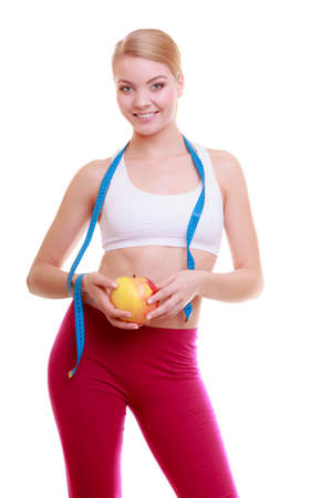 losing control: Time for diet slimming weight loss. Health care and healthy nutrition. Young fitness woman fit girl with measure tape and fruit apple isolated on white