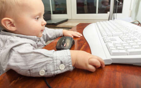elearn: Happy childhood. Smart little boy child kid playing on the desktop computer at home. Technology. Stock Photo