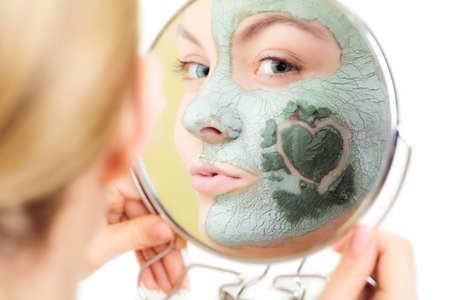 piel humana: Protecci�n de la piel. Mujer en arcilla m�scara de barro en la cara con el coraz�n en la mejilla mirando en el espejo aislado en blanco. Muchacha que toma el cuidado del cutis seco. Tratamientos de belleza.
