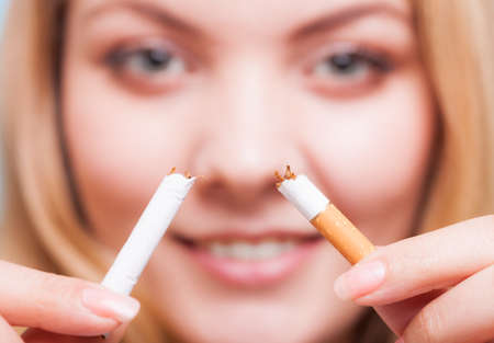 Addiction. Closeup of young woman determined girl breaking the cigarette. Quit smoking. Studio shot. photo