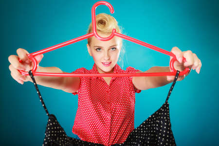 shopaholism: Pinup blond girl young woman in retro style buying clothes. Client customer holding black dotted skirt on vibrant blue. Retail and sale. Studio shot.