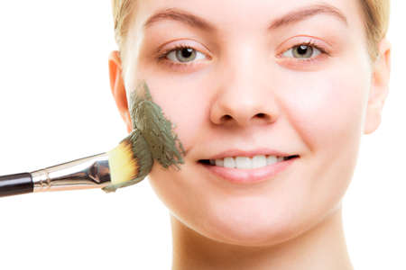 Skin care. Woman applying with brush clay mud mask on face isolated. Girl taking care of dry complexion. Beauty treatment. photo