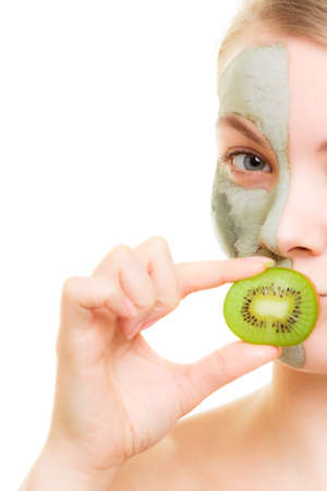 Skin care. Woman in clay mud mask on face covering mouth with slice of kiwi isolated. Girl taking care of dry complexion. photo