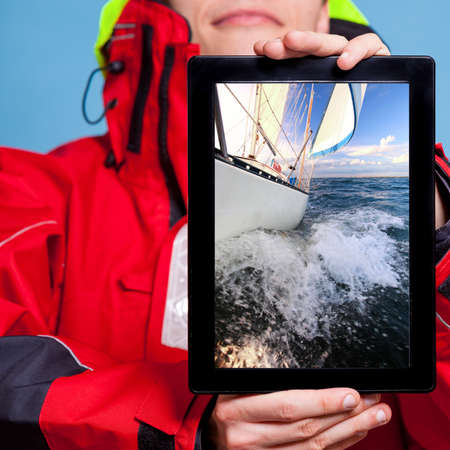 Man in wind jacket holding ipad with photo of yacht sailboat. Sailor showing screen tablet touchpad dreaming about yachting sailing. Technology and cruise. photo