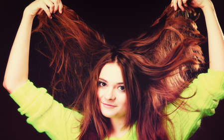 Young woman teen smiling girl having fun pulling her long brown hair on black photo