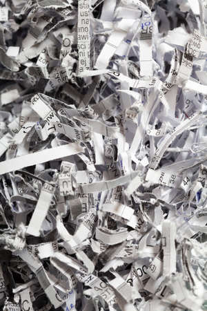 unreadable: Closeup of shredded white paper with text as abstract background or texture