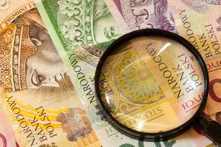 dinero falso: Concepto de dinero falsificado. Polaco billetes zloty moneda y lupa