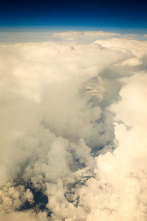 birds eye: Blue white cloudy sky. View from window of airplane flying in clouds. Skyscape cloudscape. Birds eye. Stock Photo