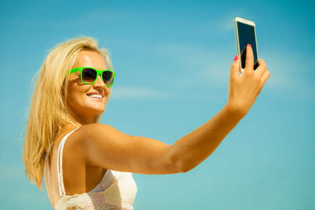 Technology internet tourism vacation concept - happy woman teen girl taking self picture with smartphone camera on beach photo