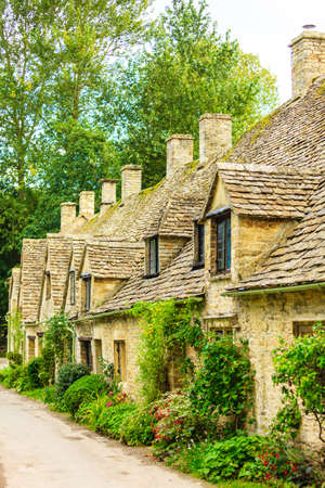 cotswold: BIBURY, ENGLAND, UK - SEPTEMBER 21, 2014: Arlington Row traditional Cotswold stone cottages in Gloucestershire on September 21, 2014, England. Bibury it the most depicted village in the world.