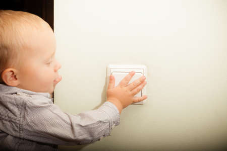 Happy childhood. Baby boy turning on or off the light. Child kid playing with switch. At home.
