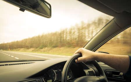 Hombre manos Conductor titular del volante de un coche y la carretera Foto de archivo