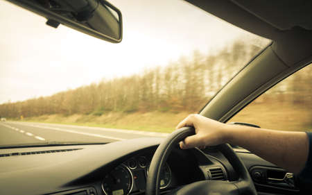 Male driver hands holding steering wheel of a car and road Stockfoto