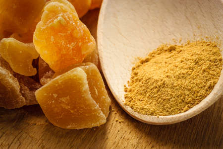 upset stomach: Ginger ground spice and candied on rustic table. Healthy eating, home remedy for nausea upset stomach colds. Stock Photo