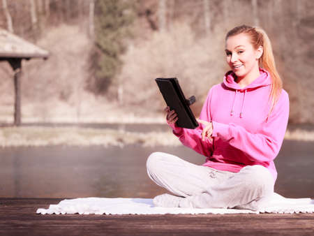 sweatsuit: Full length of fitness woman sport teenage girl in tracksuit using tablet touchpad computer sitting on pier outdoor. Electronic technology. Stock Photo