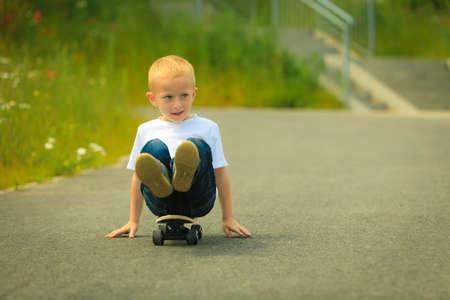 skater boy: Active childhood. Little man skateboarding. Skater boy child sits on park alley on skateboard. Outdoor.