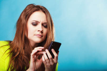sms: Technology and communication. Woman teenage girl texting on mobile phone, using smartphone reading sms message on blue