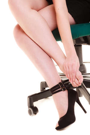 Work stoppage and leg pain. Closeup of tired businesswoman woman sitting on chair and massaging feet isolated on white. photo