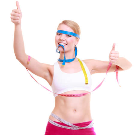 weight control: Time for diet slimming weight loss. Health care healthy lifestyle. Fit fitness woman with a lot of colorful measure tapes. Girl showing thumb up success hand sign.