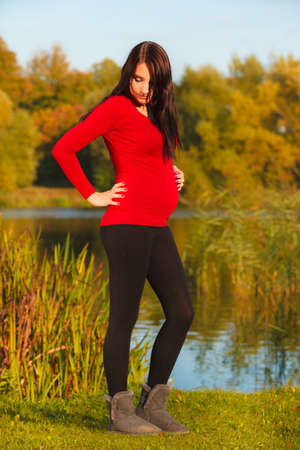 Pregnancy, motherhood and happiness concept. Relaxed calm pregnant woman walking outside in autumn park photo