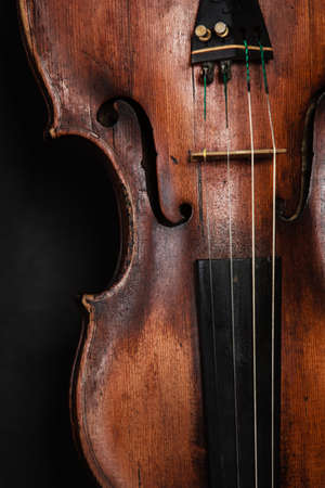 stringed instrument: Art. Closeup of old wooden violin stringed instrument on dark gray. Classical music.