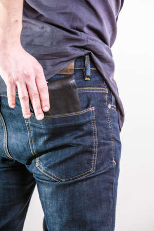 Closeup of male hands. Careless man taking the wallet out on his back pocket. Risk of theft. Isolated on white. Studio shot.