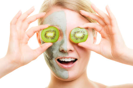 wellfare: Skin care. Surprised woman in clay mud mask with kiwi fruit on face isolated. Girl taking care of dry complexion.